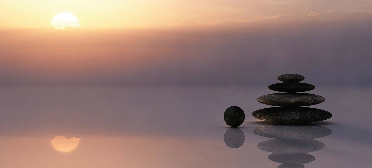 vor Meereshintergrund aufeinander gestapelte Stein, Credit: Unsplash