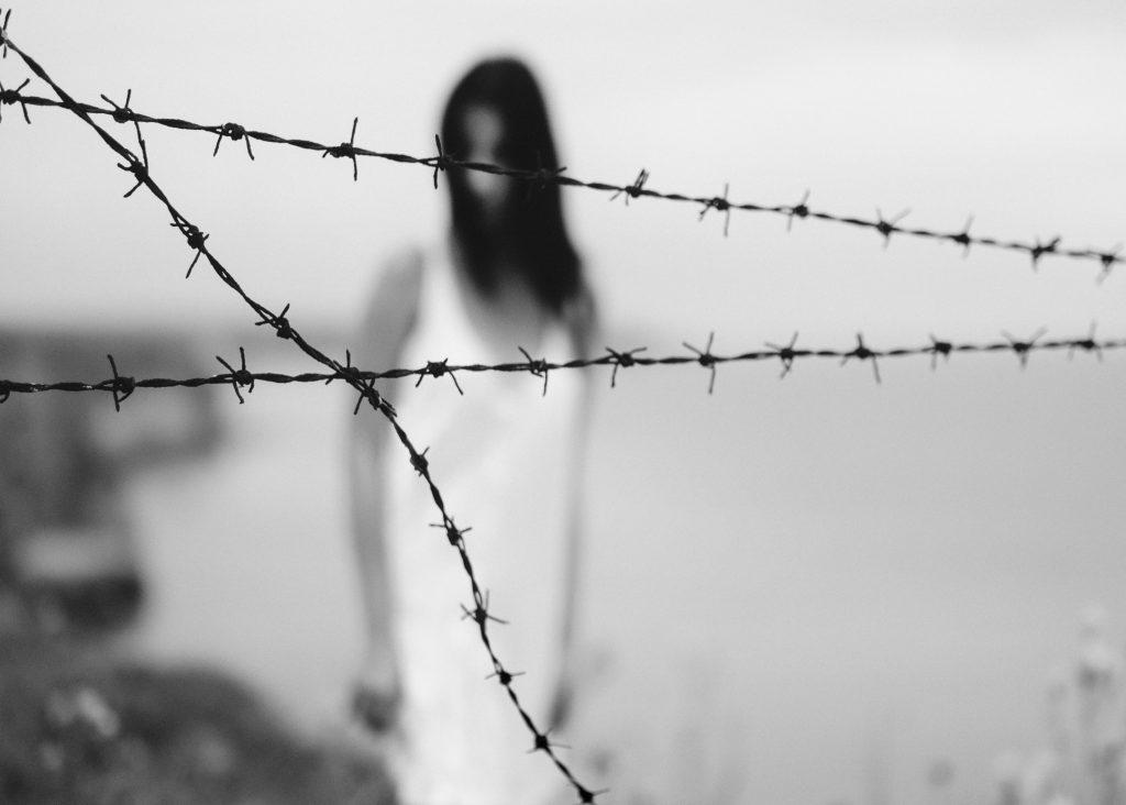 Symbolbild unsichtbare Multiple Sklerose: schwarz-weiß-Bild einer Frau hinter einem Stacheldraht, Credit: Velizar Ivanov, Unsplash