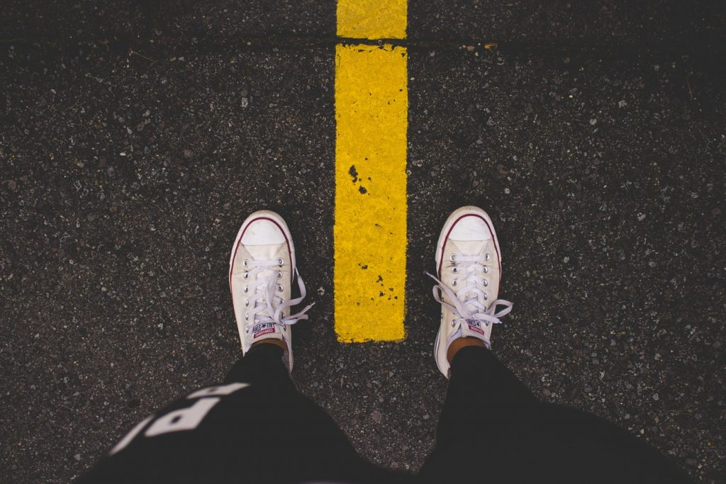 Asphaltboden mit gelber Linie, Blick nach unten auf Füße