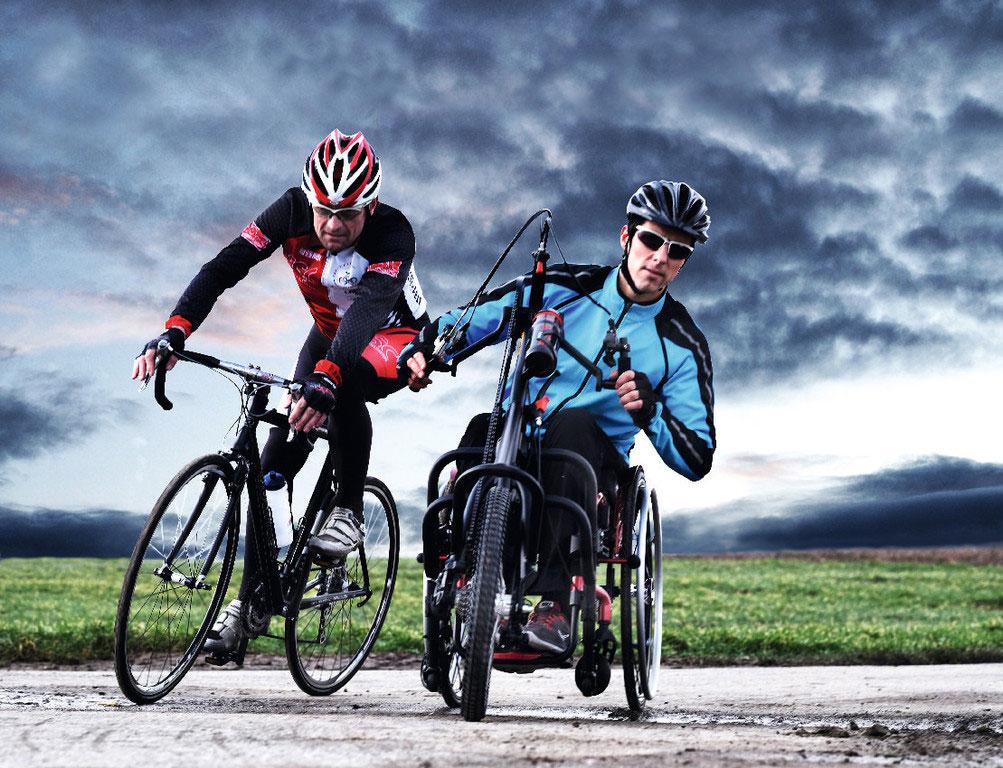 Rennrad-Fahrer und Handbike-Fahrer