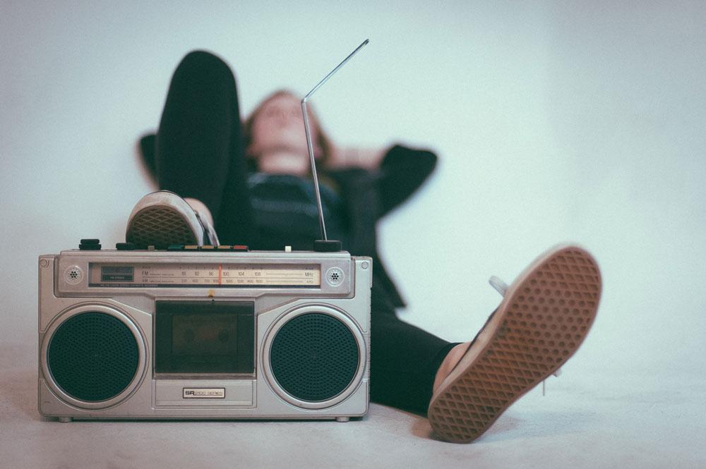 Symbolbild Entspannung: Frau liegt am Boden und legt einen Fuß auf einen Kassettenrekorder, Photo by Eric Nopanen on Unsplash