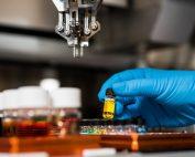 medizinisches Labor: Hand in blauem Handschuh hält kleine Flasche, Credit: Science in HD, Unsplash