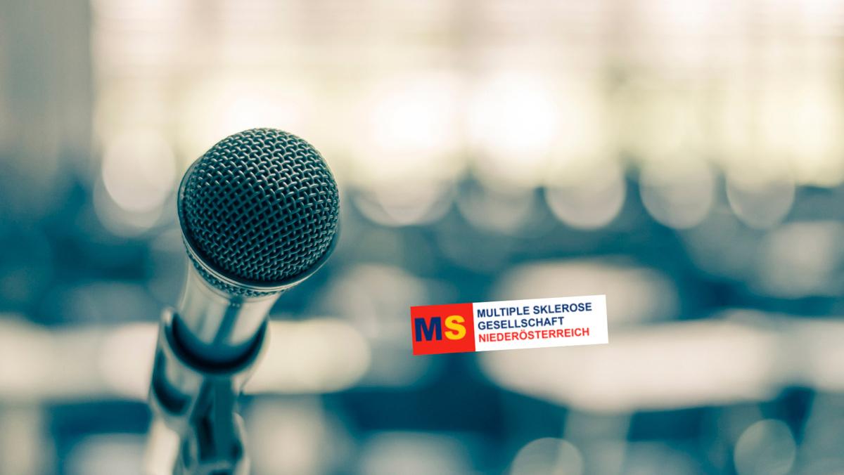 Mikrophon vor schemenhaftem Publikum mit Logo der MS-Gesellschaft Niederösterreich, Credit: Canva