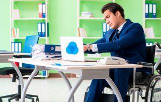 Mann mit Rollstuhl arbeitet am Schreibtisch, Credit: Canva