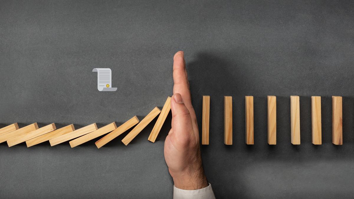 Symbolbild Risikogruppe: Männliche Hand hält Reihe von Dominosteinen auf, Credit: Canva