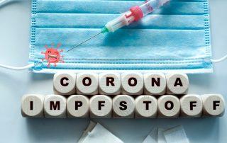 auf weißem Tisch liegen Würfel mitz dem Schriftzug Corona Impfstoffe, eine Maske und eine Spritze mit weindendem Coronavirus, Credit: Canva