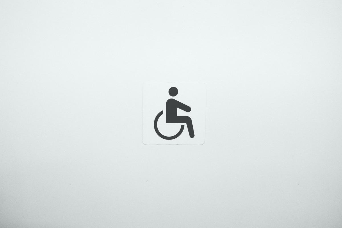 Rollstuhlsymbol auf beigem Hintergrund, Photo by Julius Carmine on Unsplash