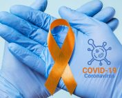 Hände in Einmalhandschuhen halten Multiple Sklerose Awareness-Schleife, Text: COVID-19-Vaccine, Credit: Canva